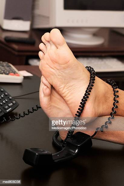 Person's feet on an office desk with a telephone cord
