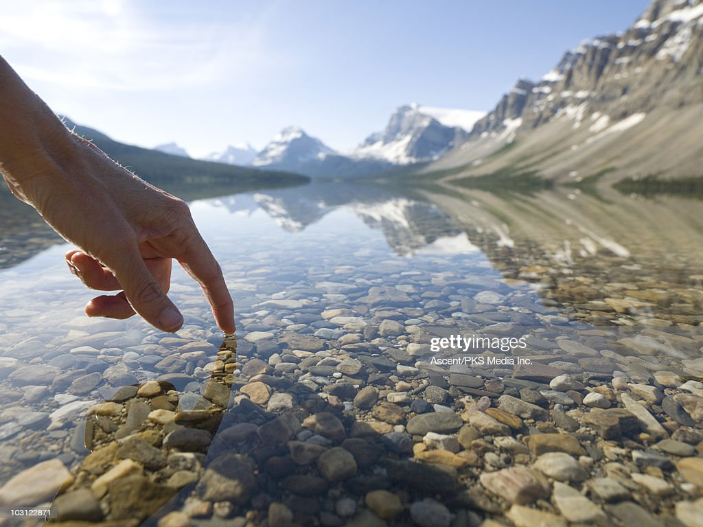 Person's finger touches calm surface of mtn lake : Stock Photo
