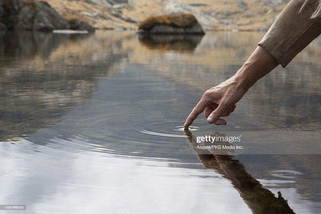 Person's finger touches surface of mountain pond : Stock Photo