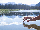Person's finger touching surface of mountain lake