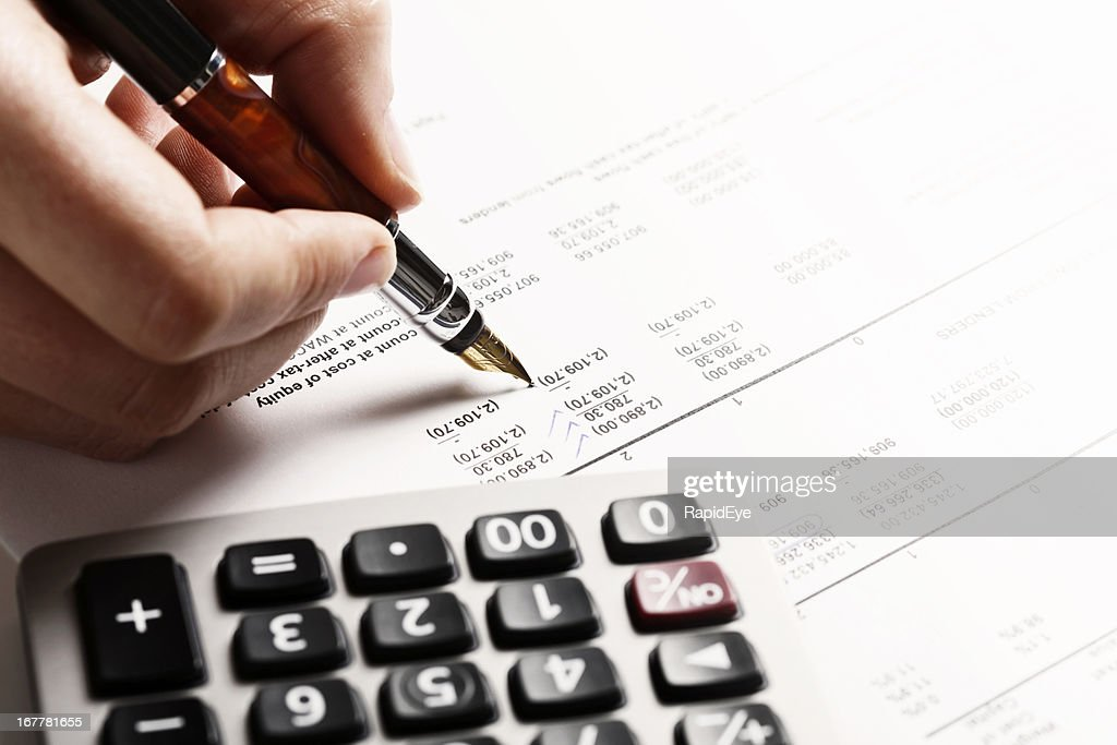 Person's hand checking figures on spreadsheet with pen and calculator