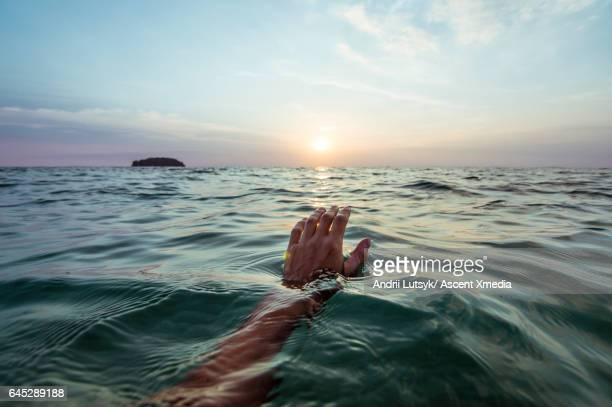 Person's hand emerges from calm water, lagoon sunrise