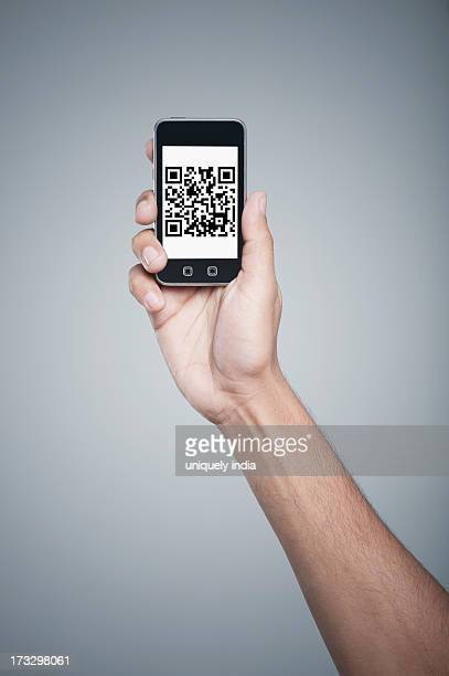 Persons hand holding a mobile phone with 2D Barcode on the screen