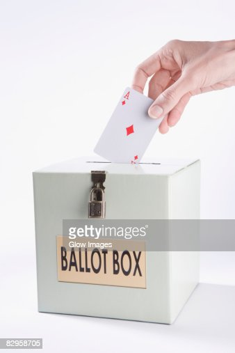 Person's hand inserting a playing card into a ballot box