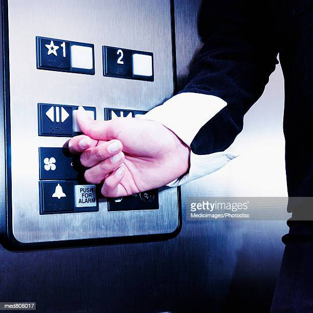 Person's hand reaching for the controls in an elevator