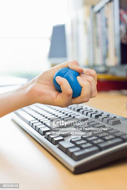 person's hand squeezing a stress ball