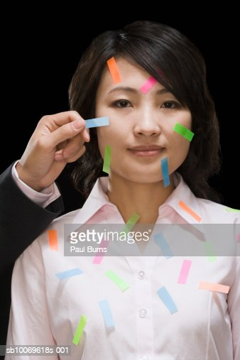 Person's hand sticking multi-colored adhesive tapes on woman's face : Stock Photo