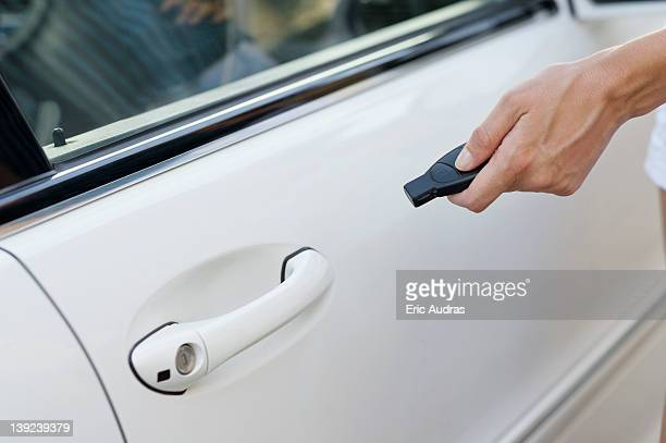 Person's hand unlocking the car with remote control