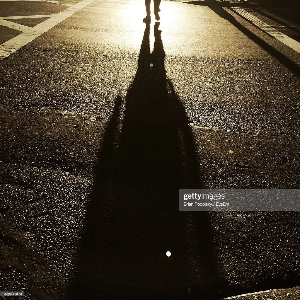 Persons Legs And Shadow On Street At Sunset