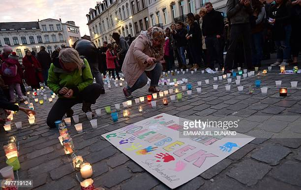 Persons light candles during a candle light vigil to the victims of the Paris attacks in Brussels' Molenbeek district on November 18 2015 Molenbeek...
