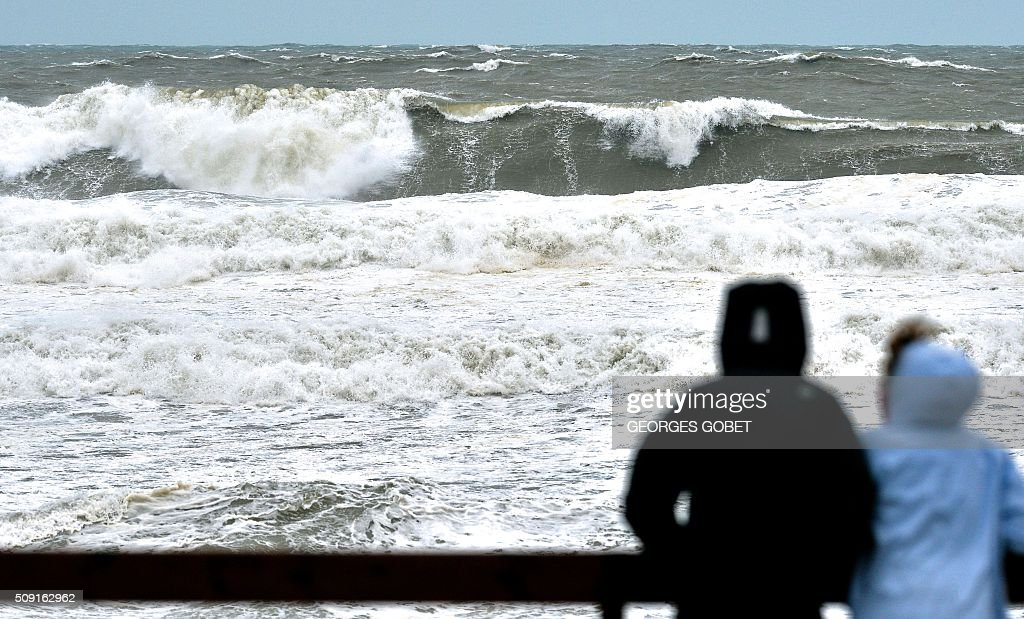 Persons look at waves at the Lacanau beach, western France, on February 9, 2016. France's Atlantic coast was lashed by powerful waves and authorities in resorts such as Biarritz took hasty measures to try to prevent the sea reaching the town. High winds buffeted northwestern Europe on February 8, leaving one woman in France in a coma after she was hit by an advertising hoarding. GOBET