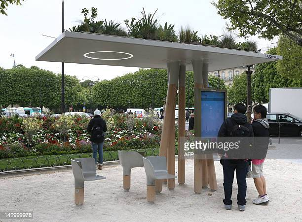 Persons read on a screen of an 'Escale Numerique' digital booth on April 17 at the ChampsElysees Roundabout in Paris by France's JC Decaux the...