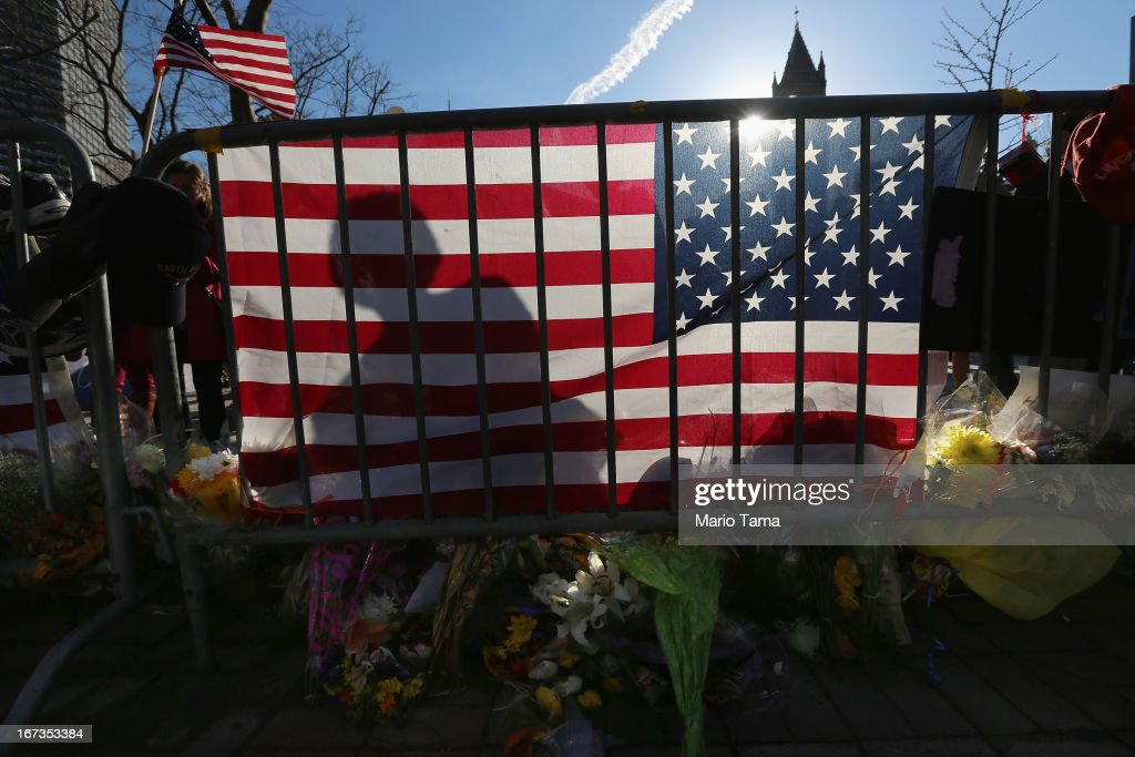 A person's shadow is cast on an American flag at a makeshift memorial in Copley Square, near the site of one of the Boston Marathon bombings, on April 24, 2013 in Boston, Massachusetts. Boylston Street, the site of both bombings, finally fully reopened to the public today along with Copley Square.