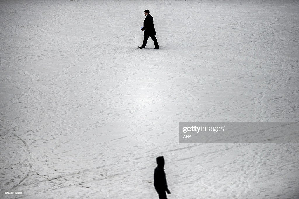 Persons walk on a snow covered street, on January 15, 2013, in a street of Lyon, central eastern France, after snow blanketed several French departments.