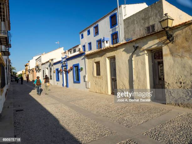 Persons walking along an ancient and tourist street of Tabarca's island  in Alicante, Valencian Community, Spain.