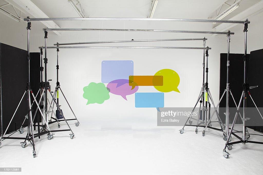 Perspex speech bubbles hanging in a studio.