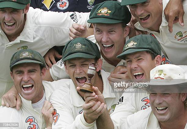 Jubilant Australian team members pose with the replica Ashes urn after winning the third Ashes Test against England in Perth 18 December 2006...