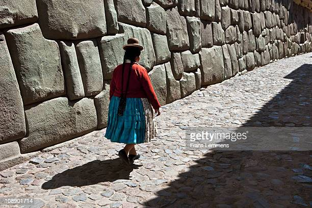 Peru, Cusco, Indian woman near ancient Inca wall