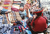 Peru, Cuzco, Chinchero, woman knitting, sitting with goods in market