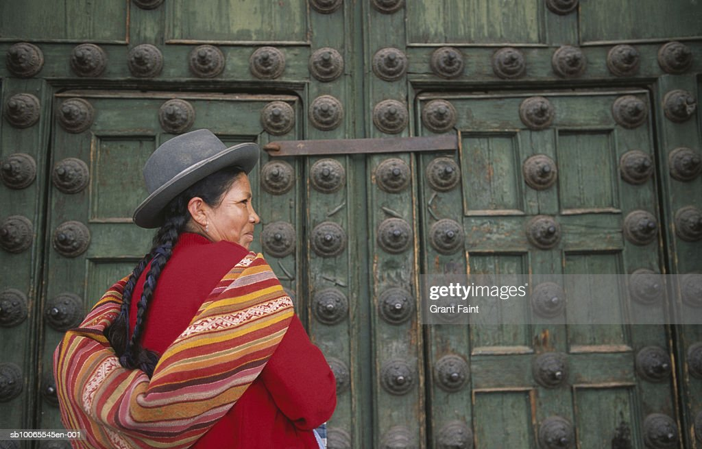 Peru, Cuzco, woman standing by Cuzco cathedral doors : Stock Photo