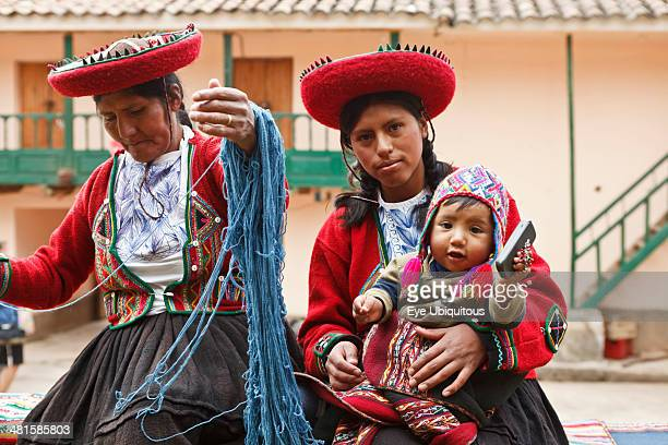 Peru Mother and baby in traditional dress with a lady making yarn and infant holding mobile phone