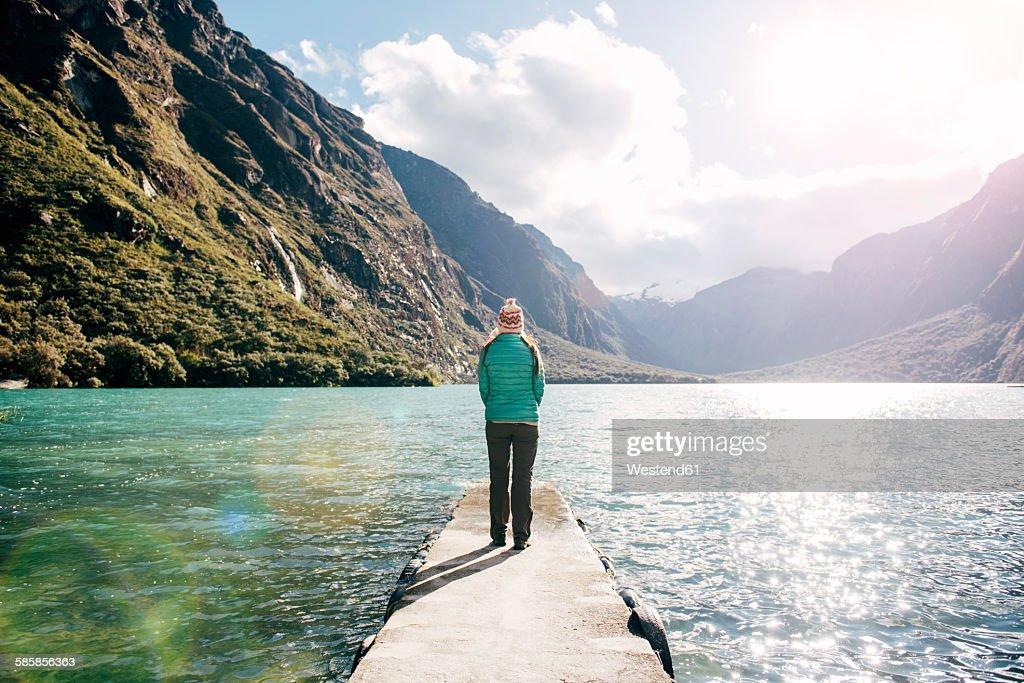 Peru, woman standing on a jetty looking at lagoon Llanganuco