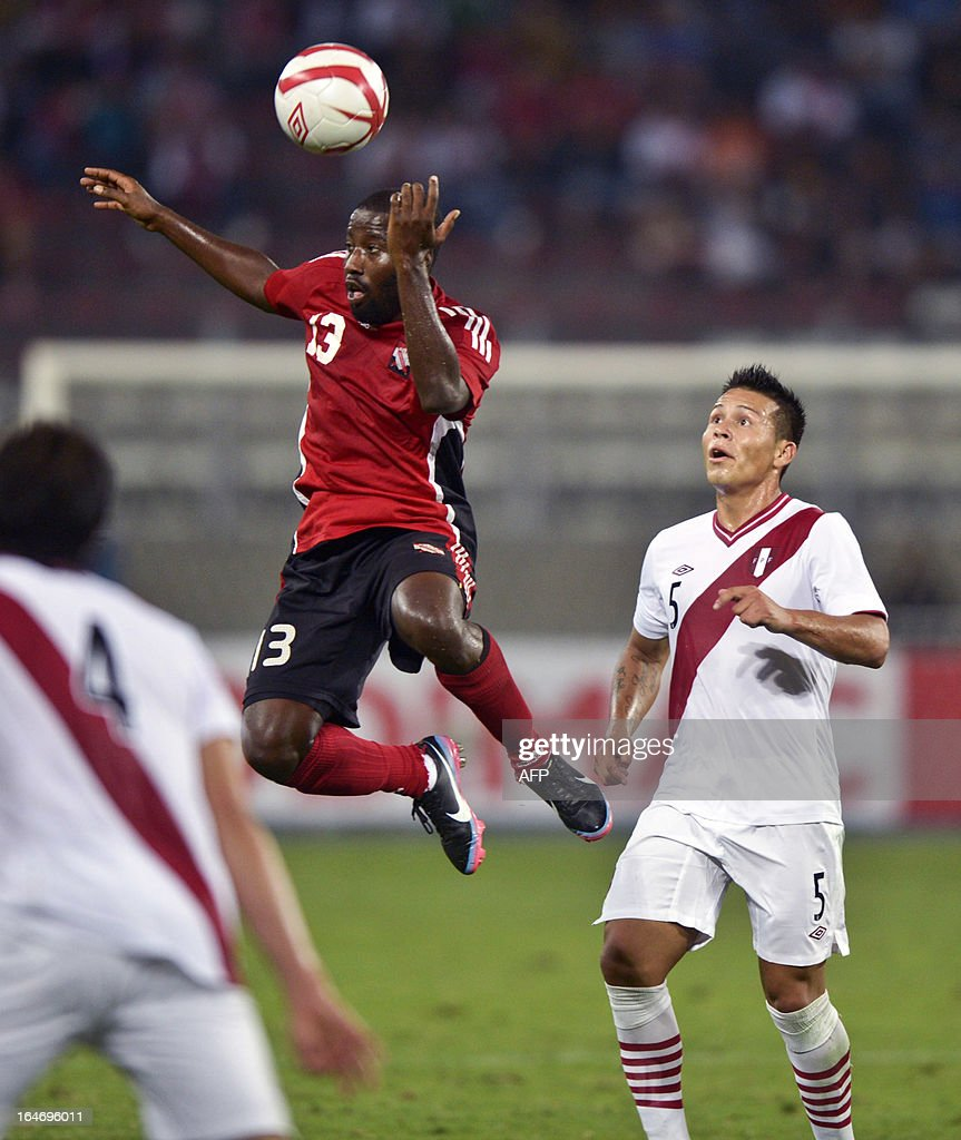 Peru's Alfredo Rojas (R) vies for the ball with Glen Cornell (L) from Trinidad & Tobago during a friendly football match at at the National stadium in Lima on March 26, 2013.