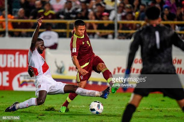 Peru's defender Christian Ramos vies for the ball with Venezuela's midfielder Darwin Machis during their 2018 FIFA World Cup qualifier football match...