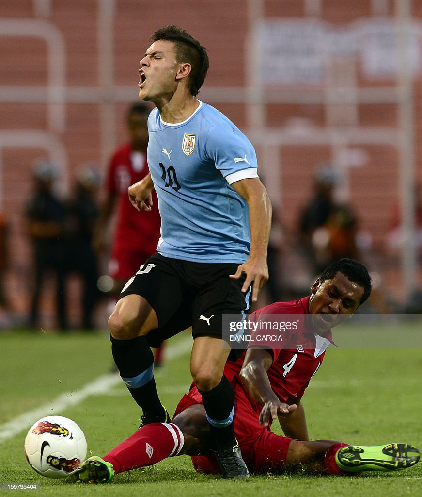 Peru's defender Renato Tapia (bottom) vies for the ball with Uruguay's forward Nicolas Lopez during their South American U-20 final round football match at Malvinas Argentinas stadium in Mendoza, Argentina, on January 20, 2013. Four teams will qualify for the FIFA U-20 World Cup Turkey 2013.