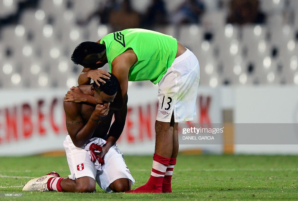 Peru's defender Renzo Chavez (R) comforts teammate defender Miguel Araujo at the end of their South American U-20 final round football match against Chile at Malvinas Argentinas stadium in Mendoza, Argentina, on February 3, 2013. Four teams will qualify for the FIFA U-20 World Cup Turkey 2013.