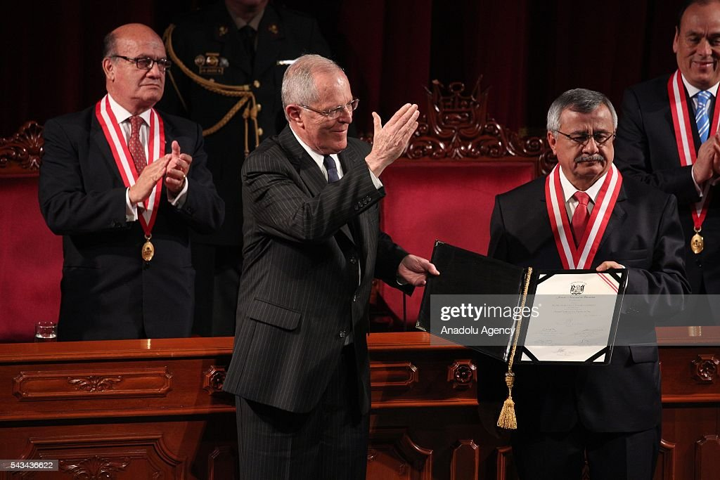 Peru's elected President Pedro Pablo Kuczynski (L) greets supporters as he receives his credentials from Francisco Tavara (R) president of the National Office of Electoral Processes, during a ceremony in Lima, Peru, Tuesday, June 28, 2016.