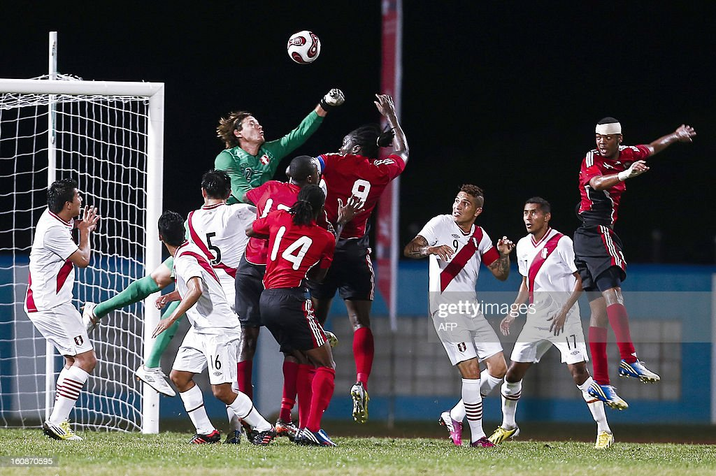 Peru's goalkeeper Diego Penny clears the ball hounded by Trinidad & Tobago players during their friendly match at Ato Bolton stadium in Couva, Trinidad on February 06, 2013,