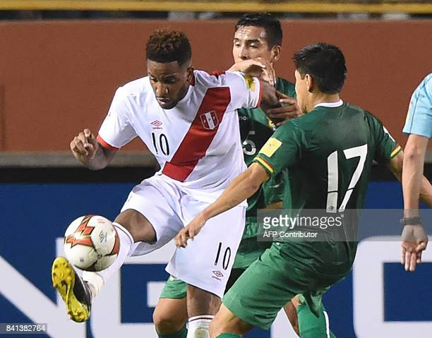 Peru's Jefferson Farfan is marked by Bolivia's Gabriel Valverde and Diego Wayar during their 2018 World Cup qualifier football match in Lima on...