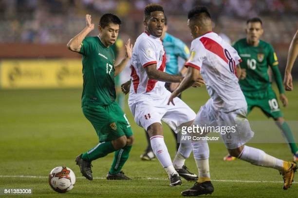 Peru's Jefferson Farfan passes the ball to teammate Christian Cueva as Bolivia's Diego Wayar gestues during their 2018 World Cup qualifier football...