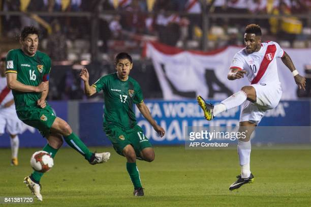 Peru's Jefferson Farfan strikes the ball as Bolivia's Ronald Raldes and Diego Wayar gesture during their 2018 World Cup qualifier football match in...