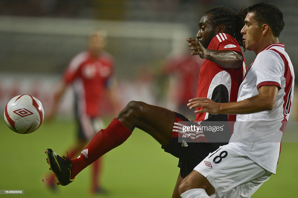 Peru's Jesus Alvarez (R) vies for the ball with Edwards Keyom of Trinidad & Tobago (L) during a friendly match at the National stadium in Lima on March 26, 2013.