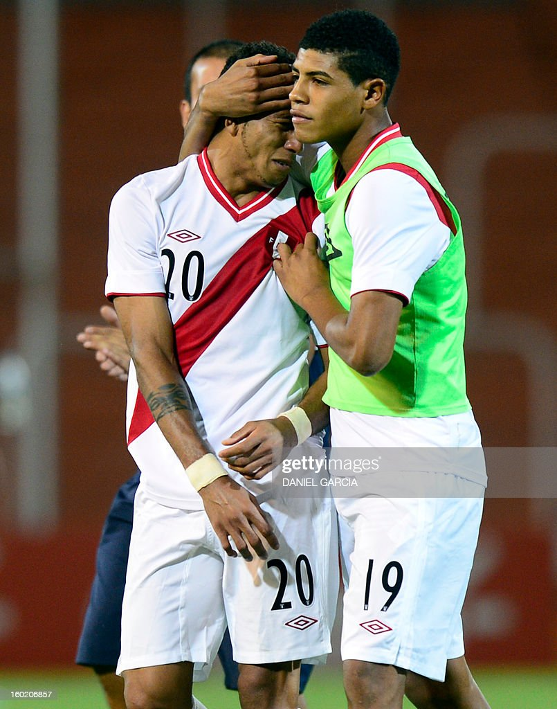 Peru's midfielder Wilder Cartagena (R) conforts teammate defender Edwin Gomez at the end of their South American U-20 final round football match against Colombia at Malvinas Argentinas stadium in Mendoza, Argentina, on January 27, 2013. Four South American teams will qualify for the FIFA U-20 World Cup Turkey 2013. Colombia won 1-0.
