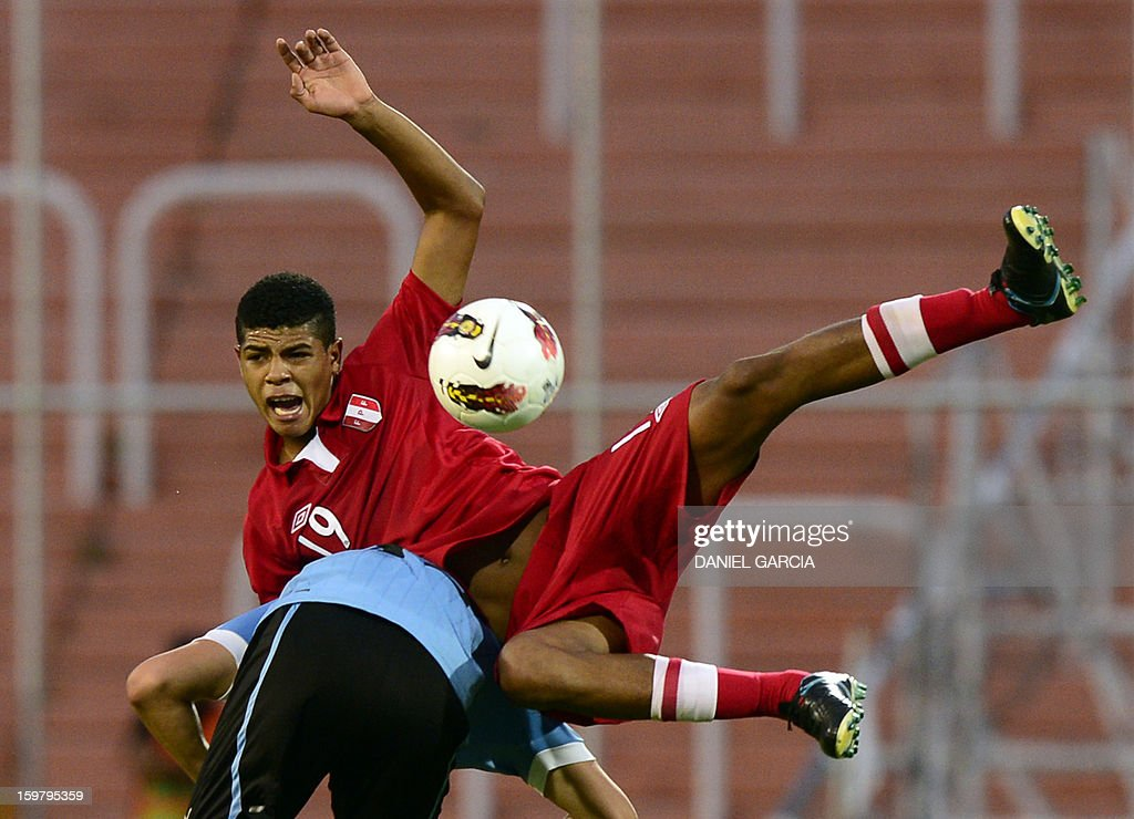 Peru's midfielder Wilder Cartagena (top) vies for the ball with Uruguay's forward Ruben Betancourt during their South American U-20 final round football match at Malvinas Argentinas stadium in Mendoza, Argentina, on January 20, 2013. Four teams will qualify for the FIFA U-20 World Cup Turkey 2013.