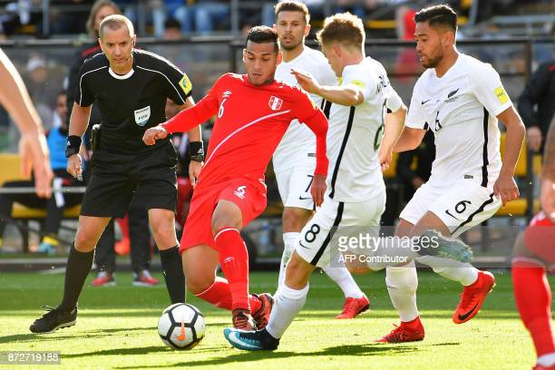Peru's Miguel Trauco dribbles the ball with New Zealand's Michael McGlinchey during the World Cup football qualifying match between New Zealand and...