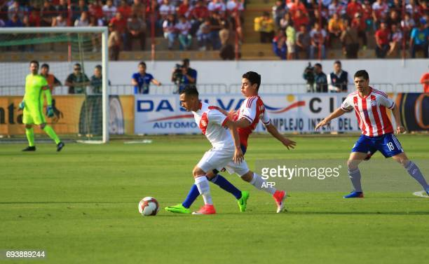 Perus national football team player Yoshimar Yotun vies for the ball with Paraguays Miguel Almiron during their friendly match played on June 8 2017...