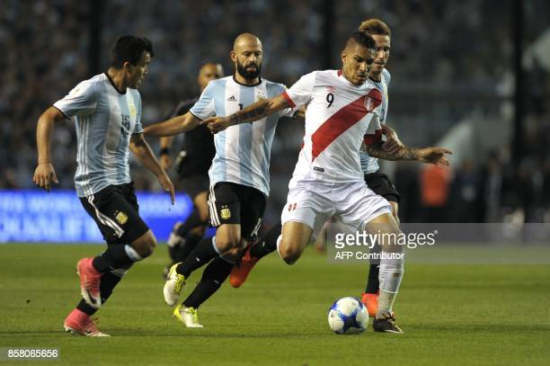 Peru's Paolo Guerrero is marked by Argentina's Marcos Acuna Javier Mascherano and Lucas Biglia during their 2018 World Cup qualifier football match...