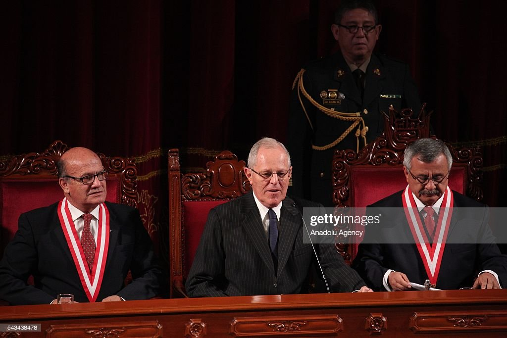 Peru's President Pedro Pablo Kuczynski, center, looks to the crowd next to Francisco Tavara, president of the National Office of Electoral Processes, right, and Jesus Fernandez Alarcon, left, after receiving his credentials from the National Office of Electoral Processes in Lima, Peru, Tuesday, June 28, 2016.