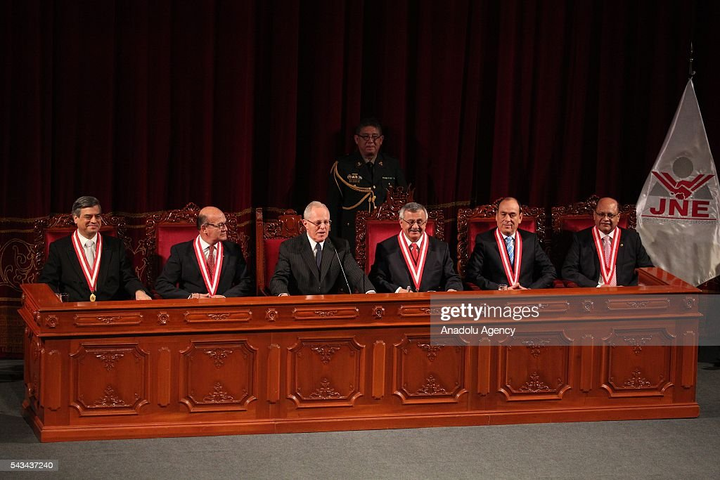 Peru's President Pedro Pablo Kuczynski, (3rd L), looks to the crowd next to Francisco Tavara, president of the National Office of Electoral Processes, (3rd R), and Jesus Fernandez Alarcon, (2nd L), after receiving his credentials from the National Office of Electoral Processes in Lima, Peru, Tuesday, June 28, 2016.