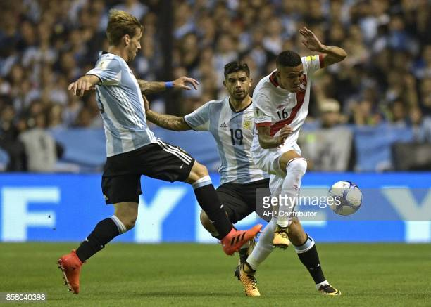 Peru's Sergio Pena is marked by Argentina's Lucas Biglia and Ever Banega during their 2018 World Cup qualifier football match in Buenos Aires on...
