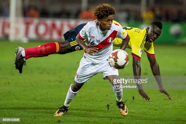 Peru's Sergio Pena vies for the ball with Colombia's Davinson Sanchez during their 2018 World Cup qualifier football match in Lima on October 10 2017...