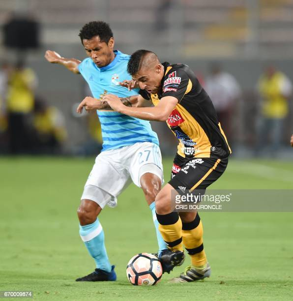 Peru's Sporting Cristal player Carlos Lobaton vies for the ball with Bolivias Strongest player Agustin Jara during their Copa Libertadores match at...