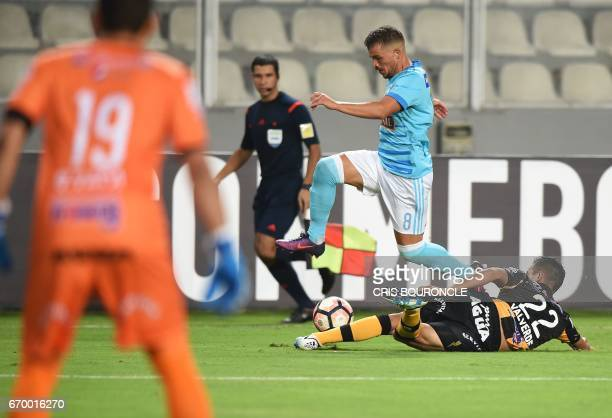 Peru's Sporting Cristal player Gabriel Costa vies for the ball with Bolivias The Strongest player Juan Valverde as Strongest goalie Daniel Vaca looks...