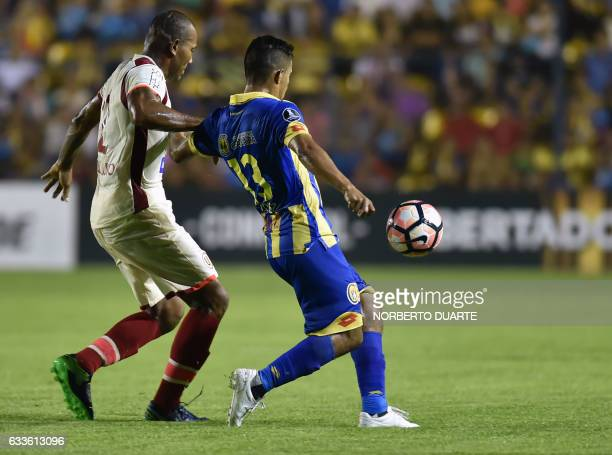 Peru's Universitario player John Galliquio and Paraguay's Deportivo Capiata's Cristian Lopez vie for the ball during their Copa Libertadores match at...