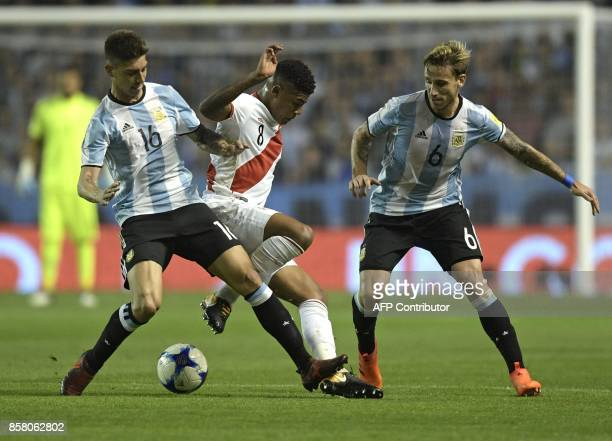 Peru's Wilder Cartagena is marked by Argentina's Emiliano Rigoni and Lucas Biglia during their 2018 World Cup qualifier football match in Buenos...