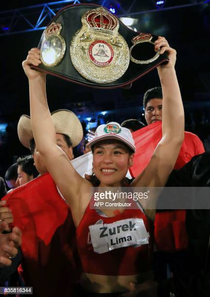 Peruvian boxer Linda Lecca raises her trophy belt after defending her World Boxing Association Super Flyweight crown for the fourth time by defeating...